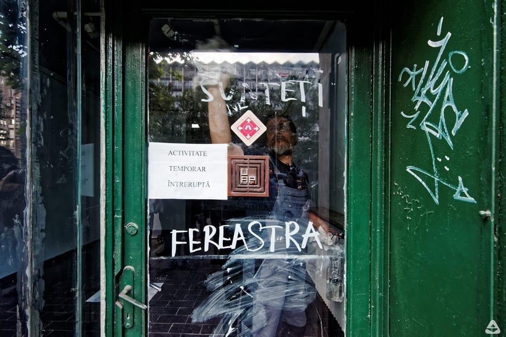 Dan Perjovschi desenează pe geamul galeriei